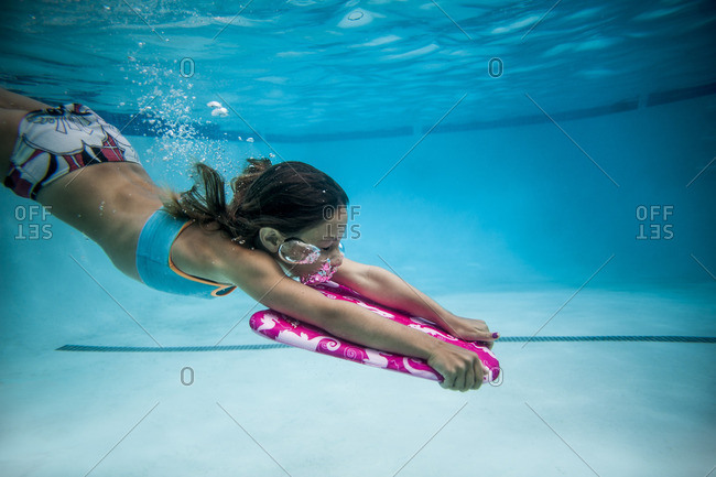 Underwater view of girl in a swimming pool with a kick board