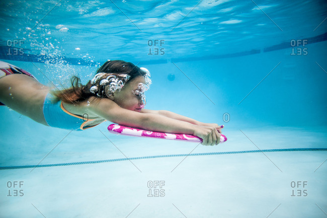 Girl in a swimming pool underwater with a kick board