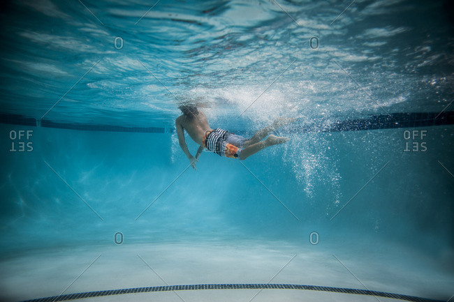 Underwater view of boy swimming at pool's surface