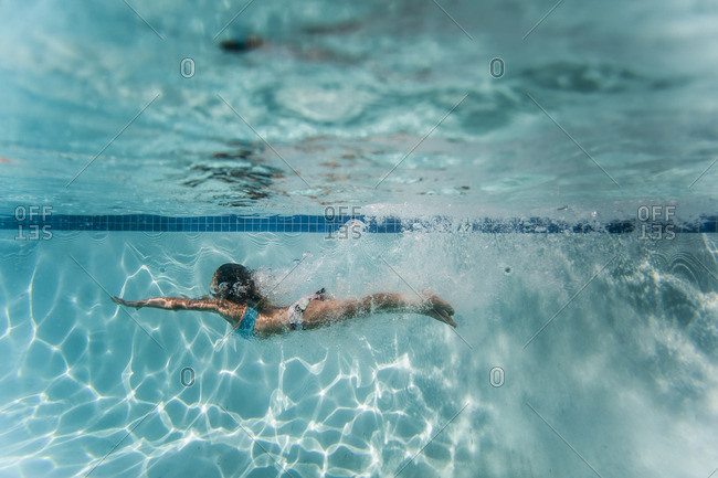 Side view of a girl swimming underwater in a pool