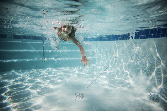 Underwater view of a little girl swimming in a pool