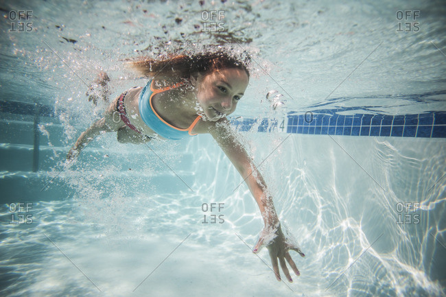 Underwater view of a young girl swimming in a pool