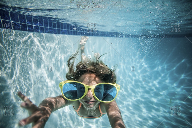 Underwater view of a girl swimming in a pool with large sunglasses