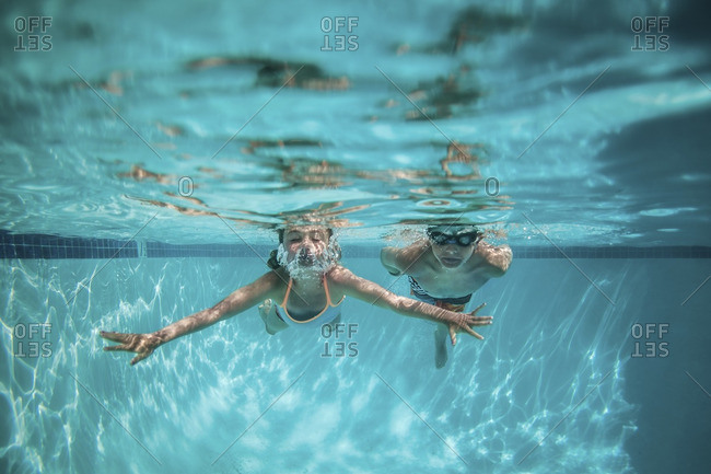 Two children swimming underwater in a pool