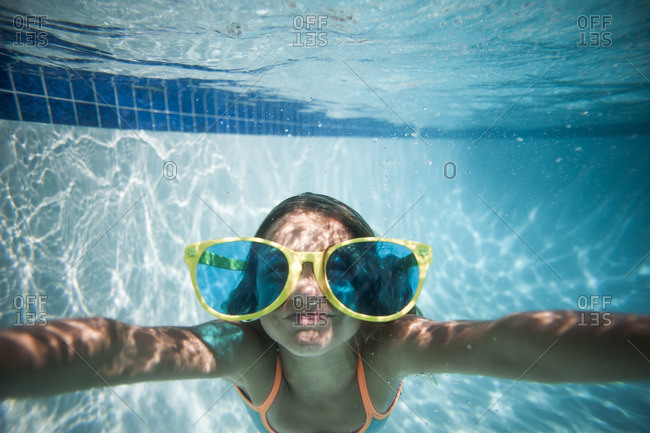 Girl swimming underwater in a pool with large sunglasses