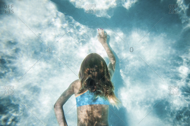 Overhead view of a girl swimming underwater in a pool
