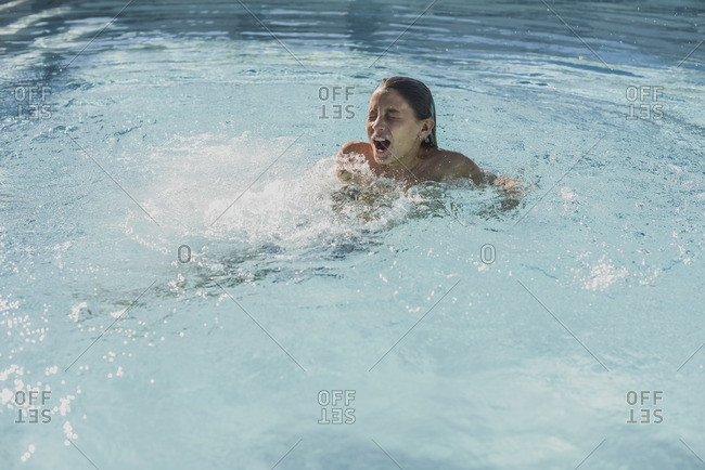 Boy getting into a cold swimming pool