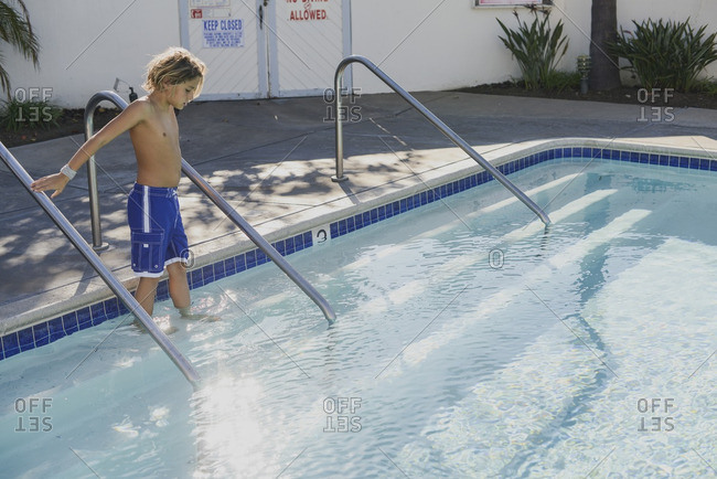 Boy holding railing while walking into a swimming pool