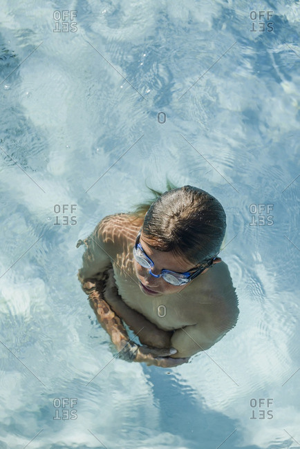 Boy standing in a pool with his arms crossed
