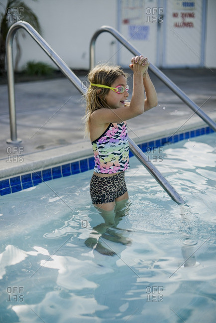 Little girl getting into in a swimming pool