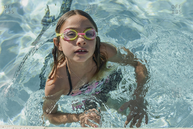 Little girl wearing goggles in a swimming pool