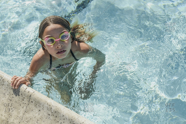 Little girl holding onto an edge of a swimming pool