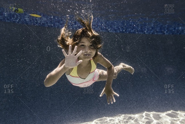 Girl waving while swimming underwater in a pool