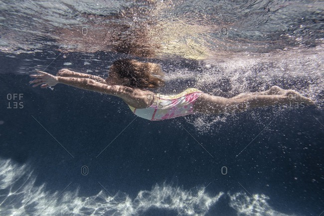 Side view of a girl swimming underwater in a swimming pool