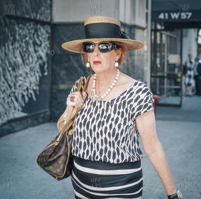 New York City, New York - February 22, 2016: Lady with a big hat and sunglasses walking on 57th Street, NYC