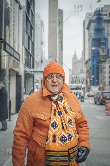 New York City, New York - February 9, 2016: Older man dressed head to toe in orange on 5th Avenue, New York City