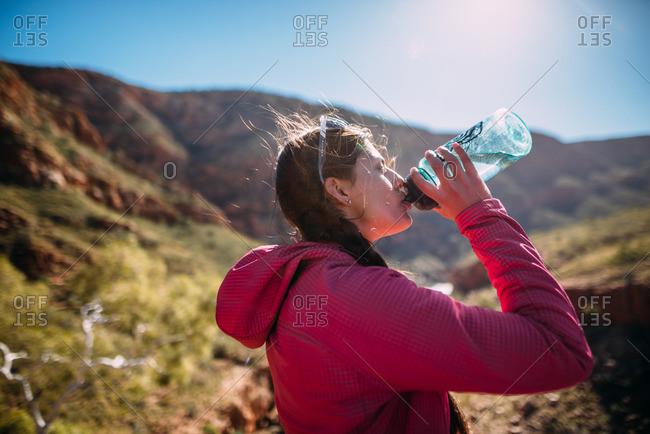 Glen Helen Gorge, Northern Territory, Australia - August 1, 2016: A woman taking a quick water break overlooking Glen Helen Gorge in the Northern Territory