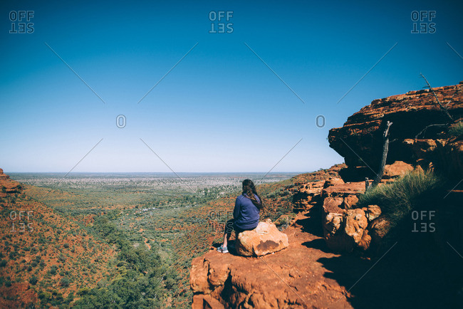 Kings Canyon, Northern Territory, Australia - August 2, 2016: A hiker looks out over the scenic landscape atop a rock formation at Kings Canyon