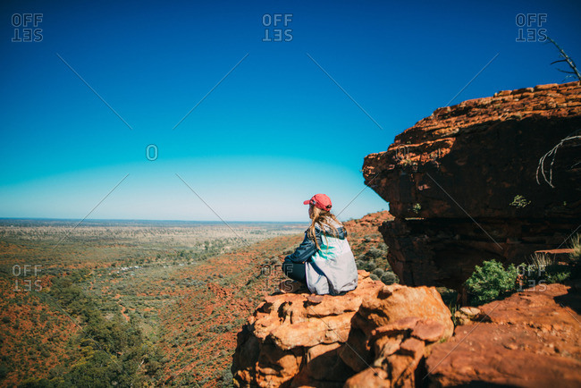 A hiker looks out over the scenic landscape atop a rock formation at Kings Canyon