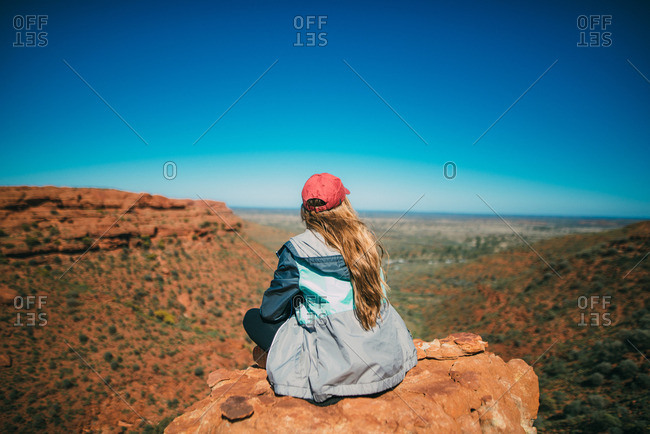 A hiker looks out over the scenic landscape atop a rock formation at Kings Canyon, Australia