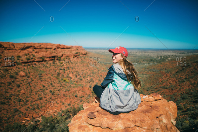 A smiling hiker looks out over the scenic landscape atop a rock formation at Kings Canyon, Australia