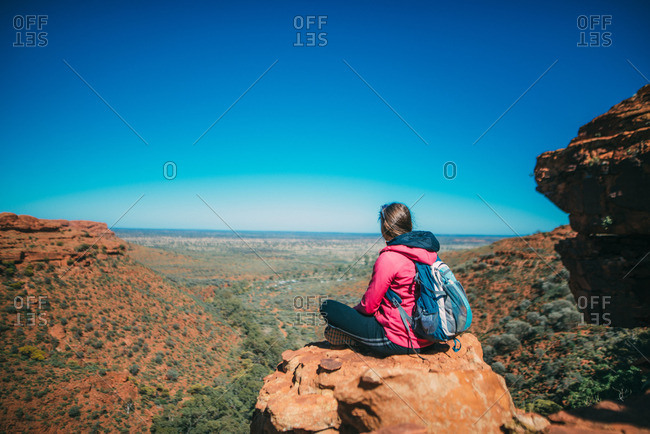 A backpacker looks out over the scenic landscape atop a rock formation at Kings Canyon, Australia