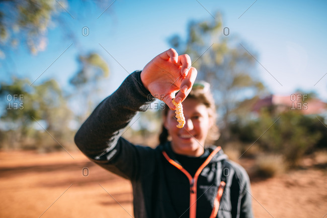Australia - August 2, 2016: A woman trying a grub worm traditionally eaten by Aboriginals