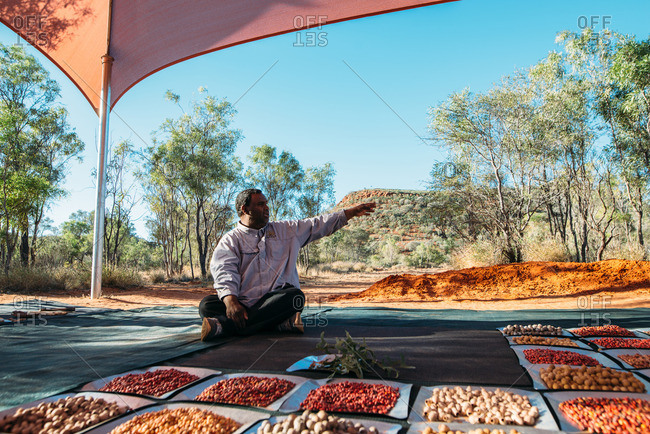 Australia - August 2, 2016: An aboriginal man teaches travellers about traditional jewelry-making customs
