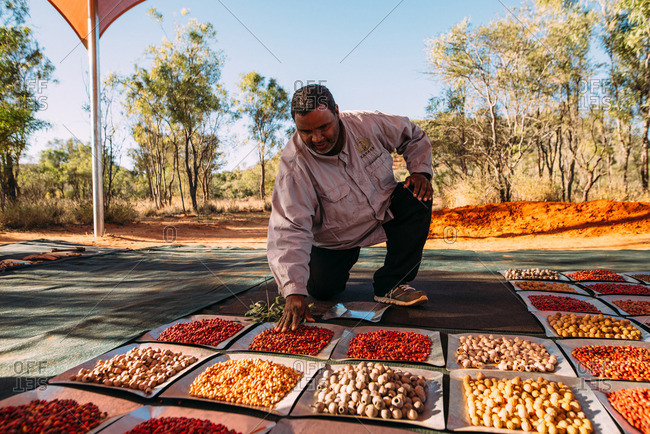 Australia - August 2, 2016: An aboriginal man instructs travellers about traditional jewelry-making customs