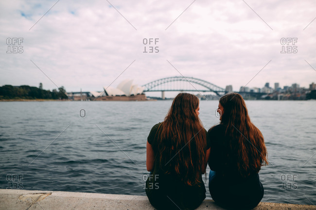 Sydney, Australia - August 6, 2016: Two friends smiling at the view of the Sydney Harbor Bridge and Opera House