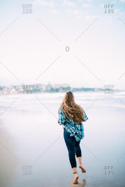 A woman runs along the coast of the famous Bondi Beach near Sydney, Australia