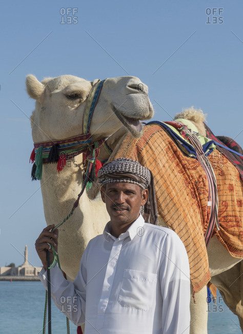 Middle Eastern man with camel near city