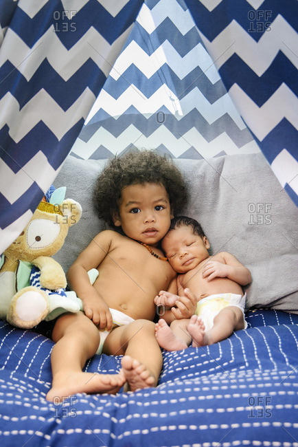 Mixed Race baby boys cuddling on bed