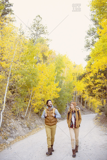 Hispanic couple hiking on path in forest