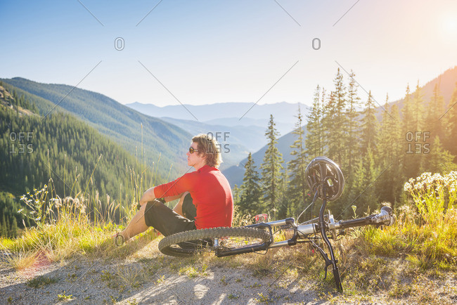 Caucasian man resting with mountain bike in mountains