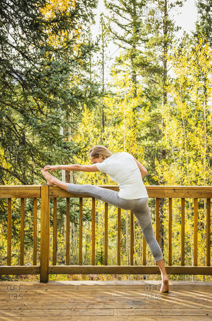 Hispanic woman stretching leg on patio fence