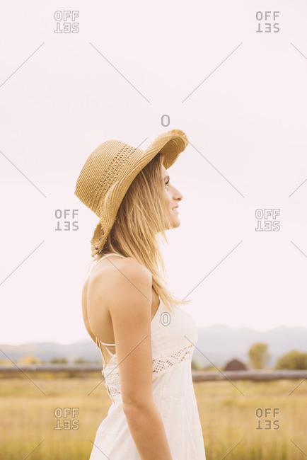 Hispanic woman wearing cowboy hat looking up