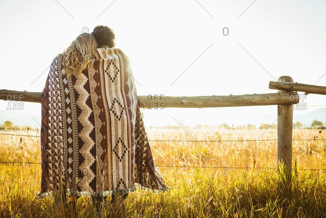 Hispanic couple wrapped in blanket leaning on fence