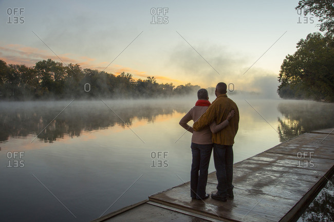 Older couple hugging at foggy river at sunrise
