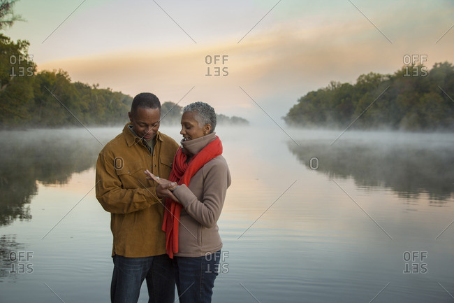 Older couple looking at ring at foggy river at sunrise