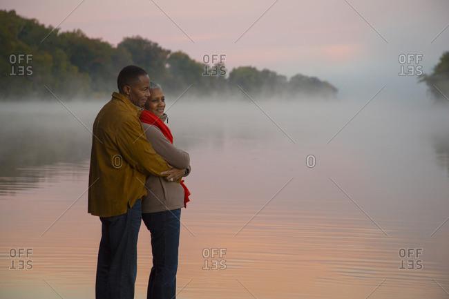 Older couple hugging at foggy river at sunrise