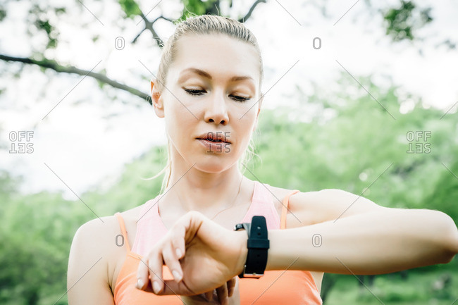 Caucasian woman checking the time on wristwatch outdoors