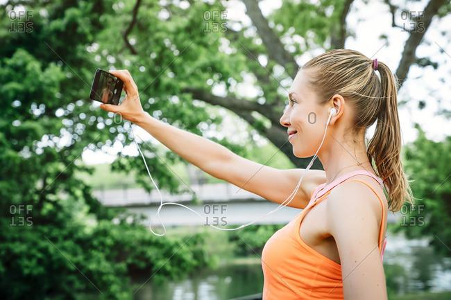 Caucasian woman using earbuds taking selfie