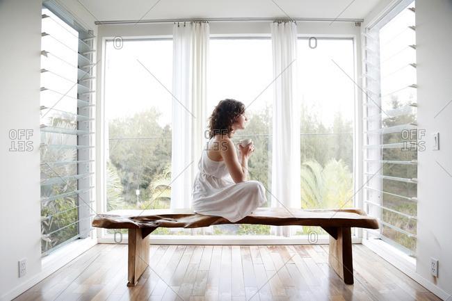 Woman drinking coffee on bench in sun room