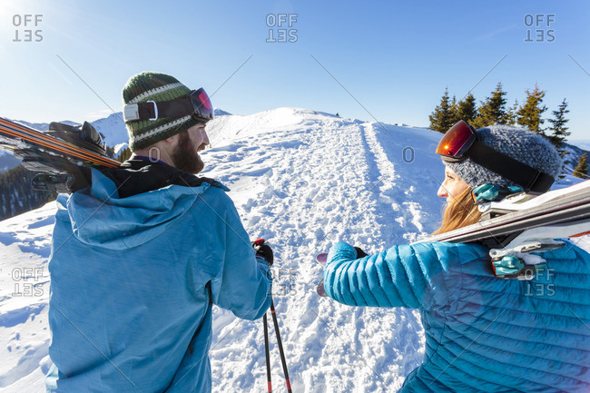 Couple carrying skis on snowy mountain