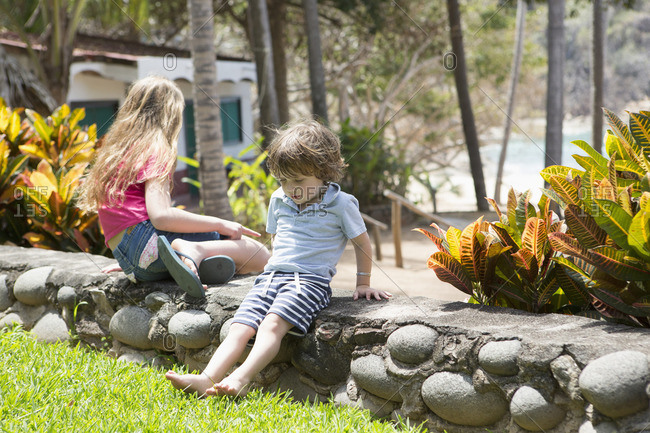 Caucasian brother and sister sitting on stone wall at beach