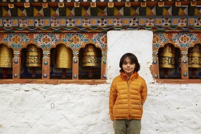 Mixed Race boy standing near prayer wheels