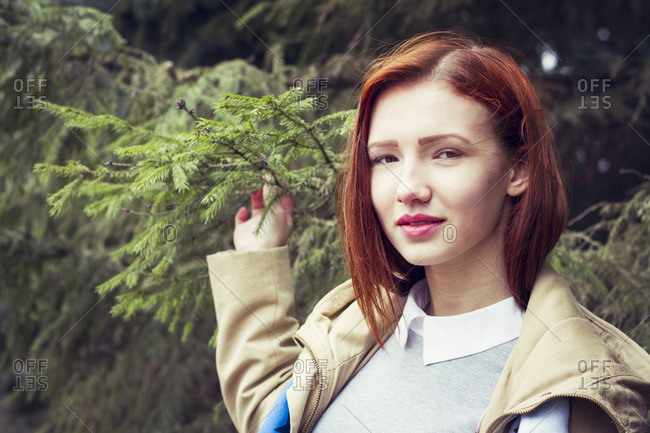 Woman with red hair holding tree branch