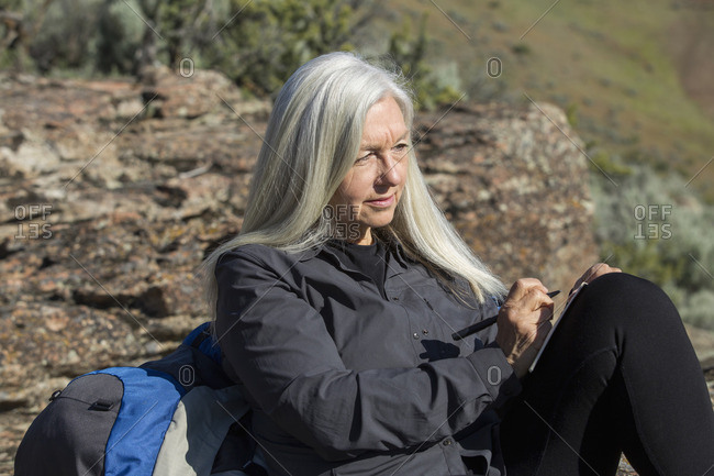 Older Caucasian woman leaning on rock writing in journal