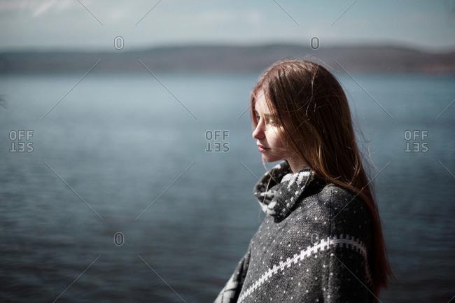 Pensive Caucasian girl at lake